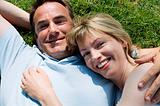 Couple lying outdoors smiling