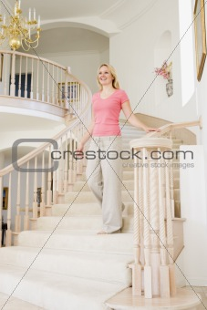 Woman coming down staircase in luxurious home smiling