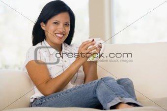 Woman in living room with coffee smiling