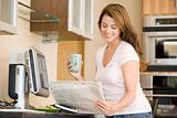 Woman in kitchen at computer with newspaper and coffee smiling