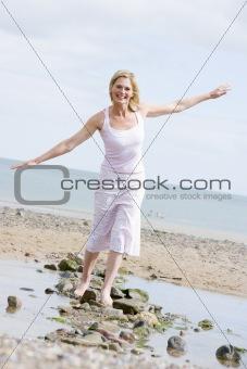 Woman walking on beach path smiling