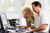 Couple in home office at computer frowning