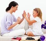 Mother with daughter sitting on sofa and playing clapping game