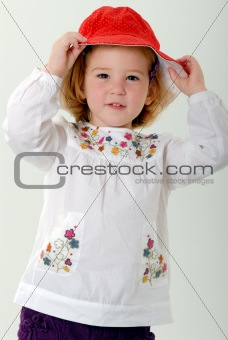 blond toddler plays with red hat