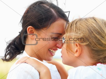 Happy young mother and daughter face to face