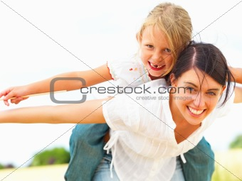 Happy young mother piggybacking her daughter