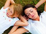 Family - Two sisters lying on grass
