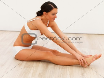 Sexy young lady exercising on floor