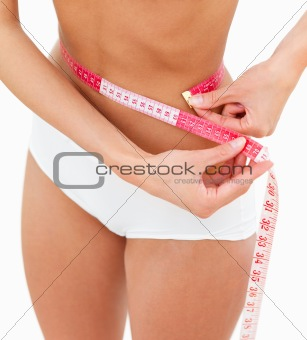 Young sexy woman measuring her waist