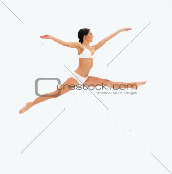 Sexy young lady jumping against isolated white background