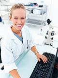 Happy female researcher sitting at a laboratory and working on c