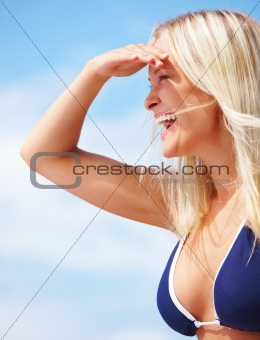 Happy young woman shielding eyes
