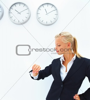 Business woman checking time in front of a wall with clocks
