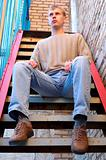 Young stylish man sit on stairs near brick wall.