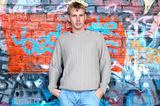 Young stylish man stand near graffiti brick wall.