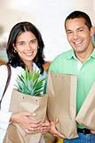Happy couple shopping in supermarket with bags