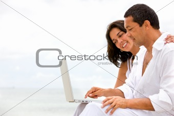 beach couple on a laptop
