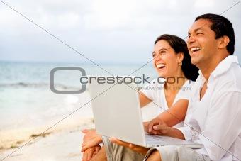 beach couple on a laptop