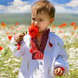 baby boy in traditional clothes in flowers