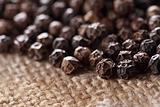 black peppercorns on a hessian background, super macro