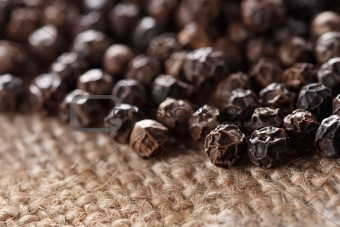 black peppercorns on a hessian background, super macro