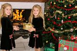 shot of children opening presents by fireplace