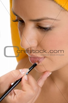 beautician putting lipstick on woman's lips