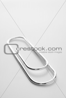 Close Up Of Silver Paperclip Against A White Background