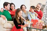 Family Sitting On Sofa In Front Of Christmas Presents,Young Girl