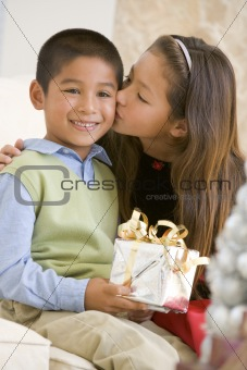 Sister Giving Her Brother A Christmas Present And Kissing Him On