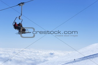 Chair lift with skiers above the clouds