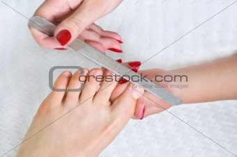applying pedicure, using nail file