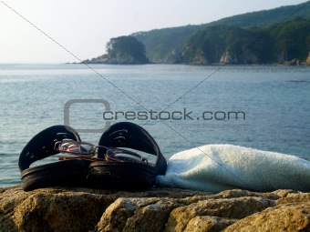 towel glasses and sandals against the seascape