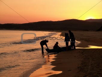 group of fisherman outward-bound against purple sunset