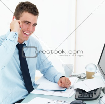 Young business man at office desk using cellphone