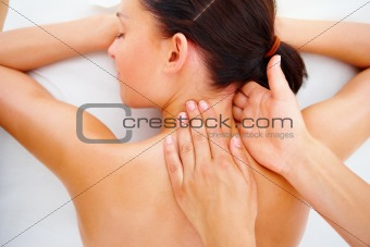 Beautiful young girl receiving shoulder massage