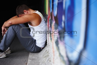 Depressed or sad young man sitting on the ground.