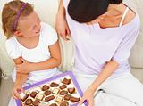 Mother with her daughter sitting on sofa with chocolate