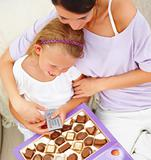 Mother with her daughter sitting  with chocolate