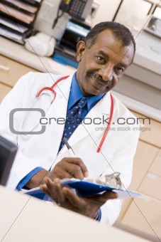 A Doctor Writing On A Clipboard At The Reception Area Of A Hospi
