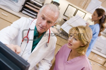 A Doctor And Nurse Discussing Something At The Reception Area Of