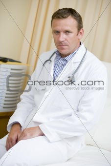 A Doctor Sitting On A Hospital Bed