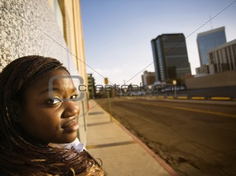 African American Woman Leaning against a Building