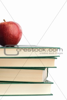A red apple on top of many books