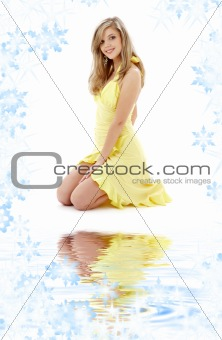 kneeled girl in yellow dress on white sand