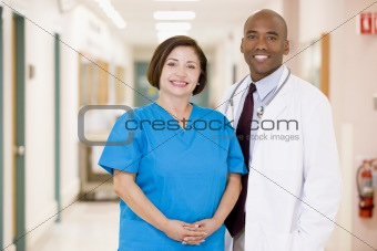 A Doctor And Nurse Standing In A Hospital Corridor