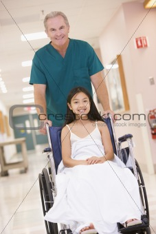 An Orderly Pushing A Little Girl In A Wheelchair Down A Hospital