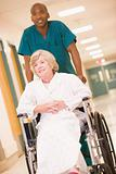 An Orderly Pushing A Senior Woman In A Wheelchair Down A Hospita