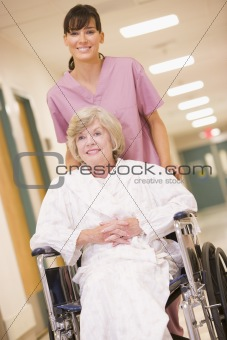 A Nurse Pushing A Senior Woman In A Wheelchair Down A Hospital C