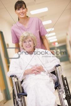 A Nurse Pushing A Senior Woman In A Wheelchair Down A Hospital C